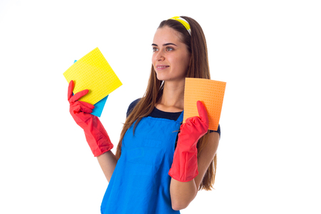 charwoman: Pretty young woman in blue T-shirt and apron with red gloves holding dusters on white background in studio