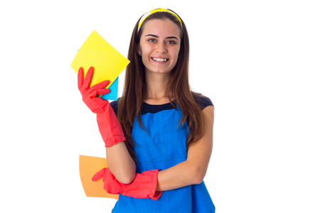 Charming young woman in blue T-shirt and apron with red gloves holding dusters on white background in studio