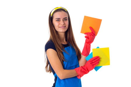 charwoman: Nice young woman in blue T-shirt and apron with red gloves holding dusters on white background in studio Stock Photo