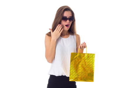 Young exited woman in white blouse and black skirt with dark sunglasses holding shopping bag on white background in studio Stock Photo