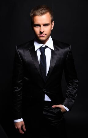 Portrait of a handsome young man in a business suit on a black background