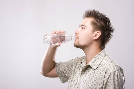 man drinking water: Young man drinking clean water from bottle Stock Photo
