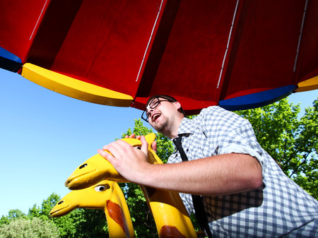 Droll young man in glasses sitting on giraffe in merry-go-round