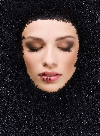 Face of young beauty woman in black caviar