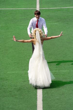 Bride and groom on football stadium