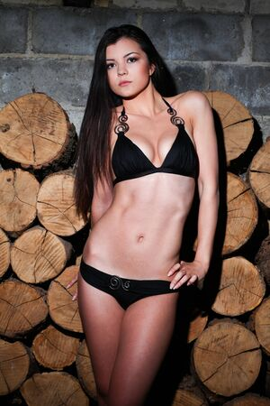 Young woman in a black swimsuit standing elegant. Background of firewood