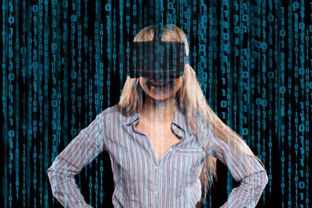 Intrigued woman in grey shirt wearing virtual reality 3D headset and exploring the play on black background