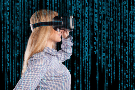 Profile view of intrigued woman in grey shirt wearing virtual reality 3D headset and exploring the play on black background