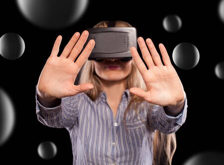 immersed: Young woman immersed in interactive virtual reality video game doing gestures on black background.