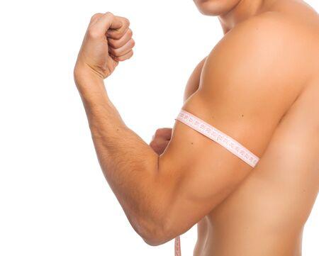 Shirtless man measuring his biceps with centimeter Stock Photo
