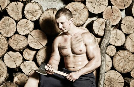 hatchet man: Young strong man with hatchet and a lot of woods Stock Photo