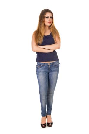 jeans apretados: La mujer en jeans ajustados azules está con los brazos cruzados sobre el fondo blanco.