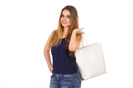jeans apretados: Mujer sonriente en jeans ajustados azules con el bolso blanco está de pie en el fondo blanco.