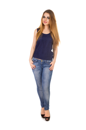 The woman in blue tight jeans is holding her big fingers in her  pockets on the white background.