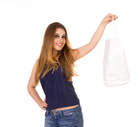 jeans apretados: Smiling woman in tight blue jeans with white handbag is standing on the white background.
