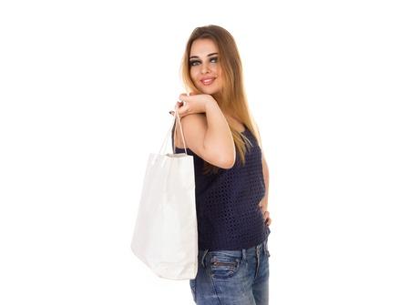 jeans apretados: Sonriendo hermosa mujer en jeans ajustados azules con el bolso blanco está de pie en el fondo blanco.