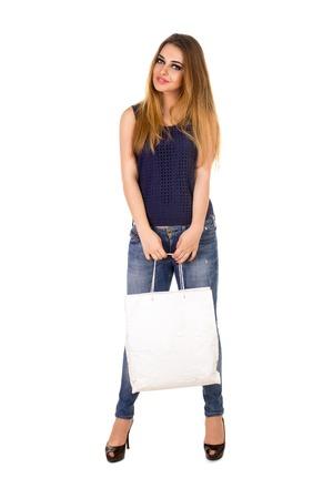 jeans apretados: La mujer en jeans ajustados azules con el bolso blanco en sus manos está de pie sobre el fondo blanco. Foto de archivo