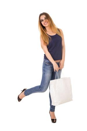 jeans apretados: La mujer en jeans ajustados azules con el bolso blanco en sus manos está de pie sobre los talones en el fondo blanco.
