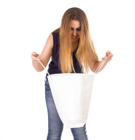 jeans apretados: La mujer en jeans ajustados azules con el bolso blanco en sus manos está investigando sobre el fondo blanco. Foto de archivo