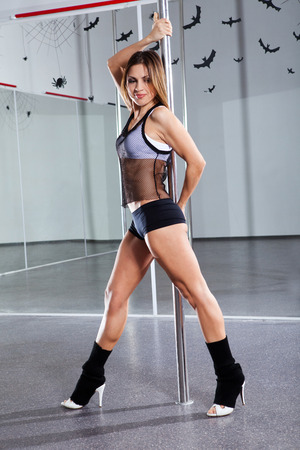 Young athletic woman dancing around the pole