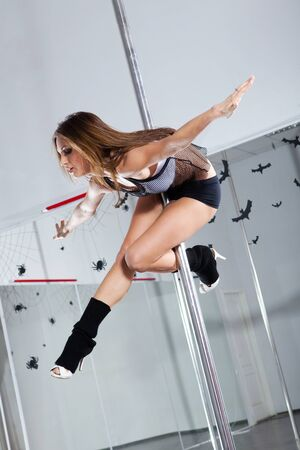 stripper pole: Young athletic woman dancing around the pole