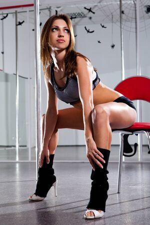 beine spreizen: Schöne Frau in einem Anzug für die Pole-Tanz auf einem Stuhl sitzend mit ihren gespreizten Beinen Lizenzfreie Bilder