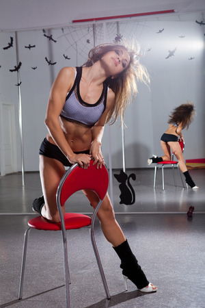 Sexy woman in a suit for the pole-dance setting her knee against the chair Stock Photo