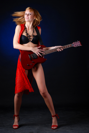 portrait of a young woman with red electric guitar