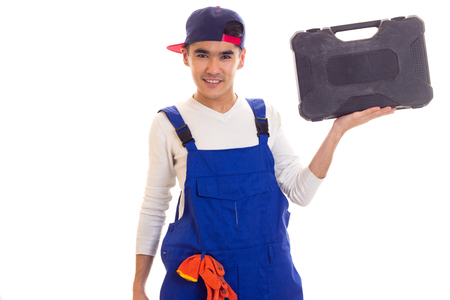 Young man in overall holding toolbox