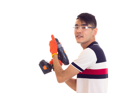 Young man with gloves and glasses holding electric screwdriver Stock Photo