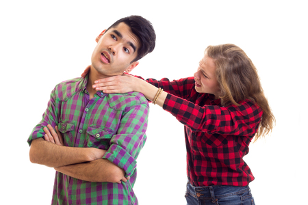 Young angry woman with long chestnut hair strangling young handsome man with dark hair in plaid shirts arguing on white background in studio Stock Photo