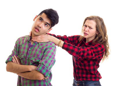 Young angry woman with long chestnut hair strangling young nice man with dark hair in plaid shirts arguing on white background in studio