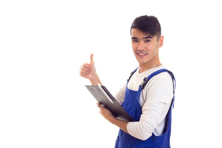 overol: Young man in blue overall holding pen and folder Foto de archivo