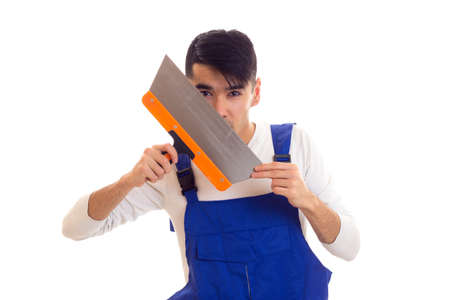 Man in blue overall holding spatula