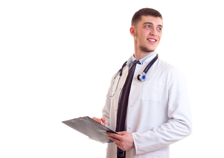 Happy young man with chestnut hair in blue shirt, tie and white doctor gown with stethoscope on his neck writing in his black folder on white background in studio