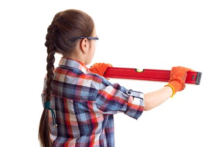 Little girl with long chestnut pigtail in plaid red shirt with orange gloves and glasses holding building level on white background in studio