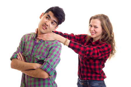 Young miling woman with long chestnut hair strangling young handsome man with dark hair in plaid shirts arguing on white background in studio Stock Photo