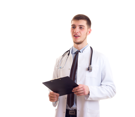 Young smartlooking man with brown hair in blue shirt, tie and doctor gown with stethoscope on his neck holding black folder on white background in studio
