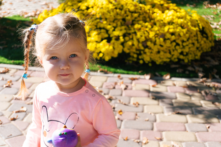 Little girl standing near plants in park
