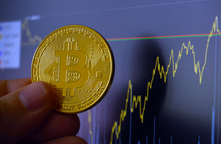 Digital currency of future Bitcoin. Golden BTC coin in front of charts