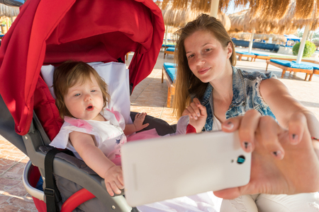 Mother taking selfie with baby girl on resort