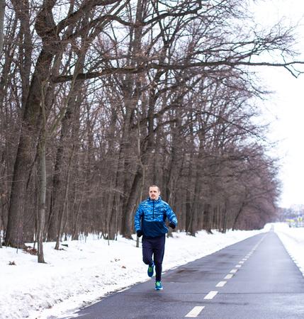 Runner man in blue running wear run in winter time