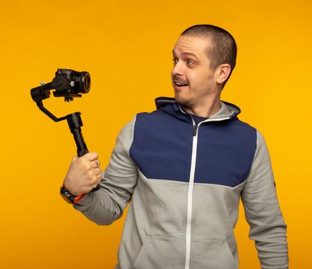 Man vlogger or videographer filming self using camera on gimbal