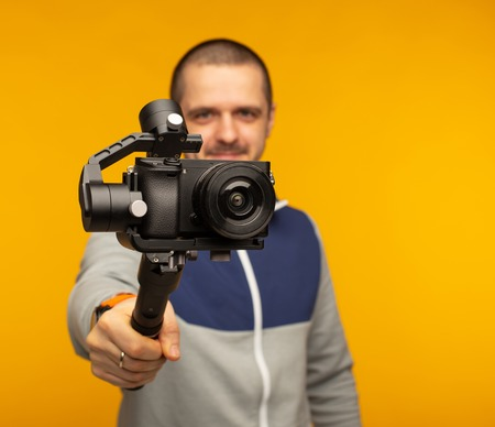 Man with camera on gimbal recording something
