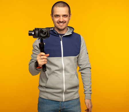 Man videographer or blogger with camera on gimbal Stock Photo