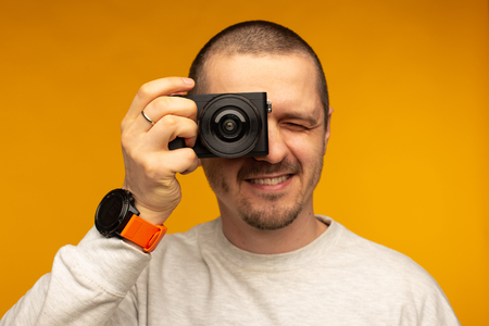 Man put camera to his eye. Photographer or videographer