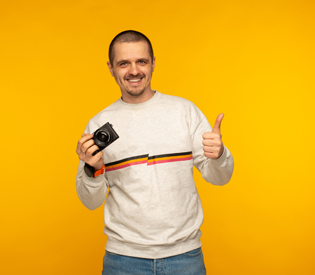 Man photographer or blogger holding camera and show thumbs up