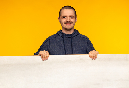 Smiling man holding wooden white empty board in hands