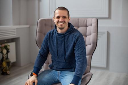 Man in dark blue hoodie smiling and looking in camera Stock Photo
