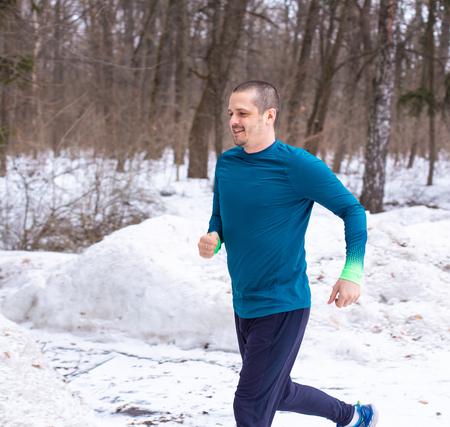 Runner adult man running outdoor in winter Stock Photo